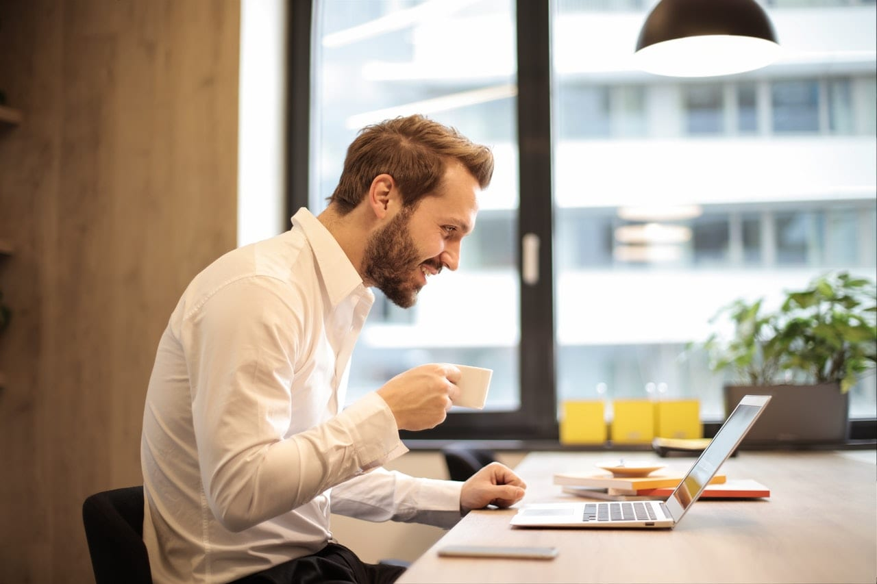 4 informações que todo portfolio precisa ter. Homem sorridente trabalhando com um laptop, tomando um cafezinho.