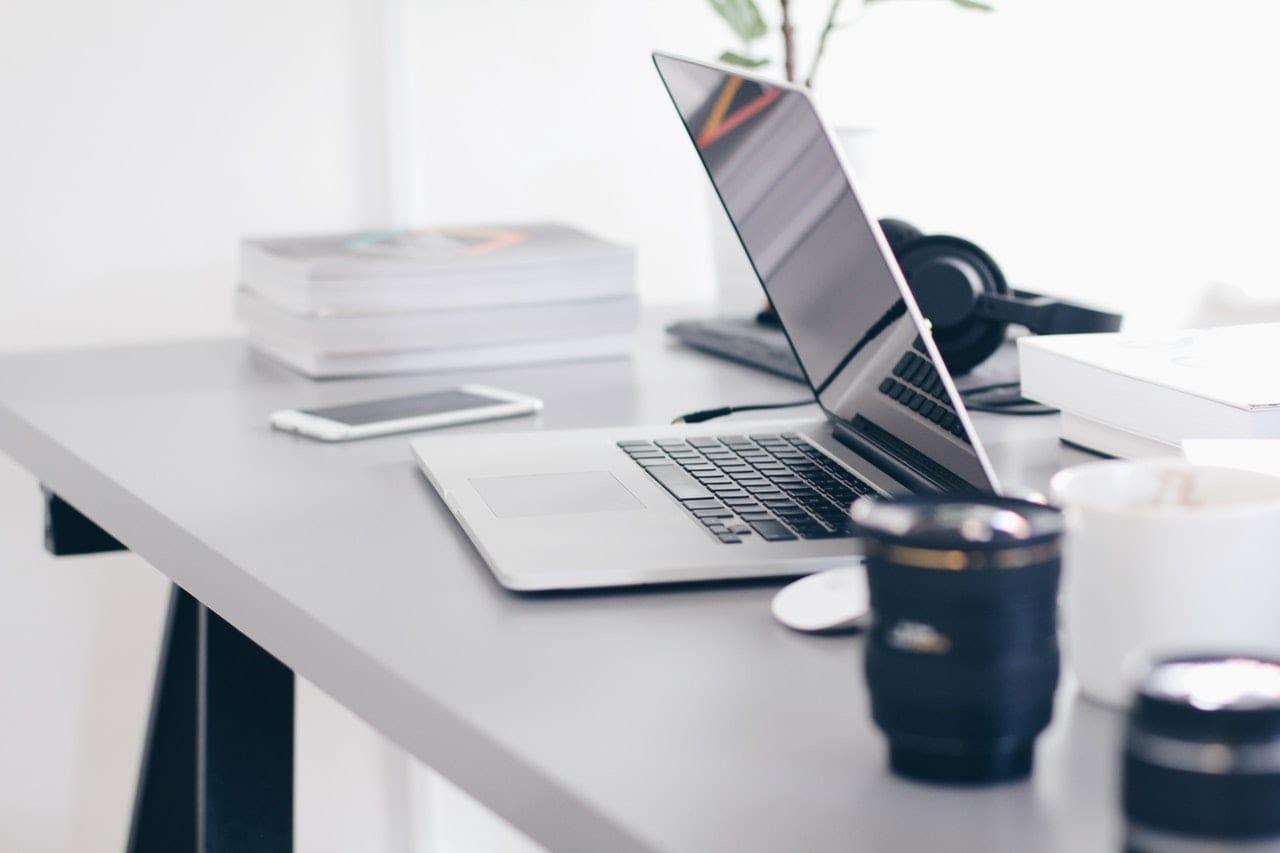 Por que algumas pessoas têm bons portfolios e outras não? Imagem mostrando uma mesa com um notebook e algumas lentes de câmera.