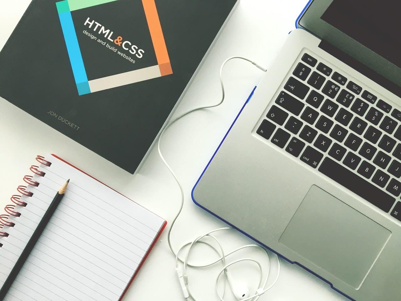 Portfolio com foco em desenvolvimento web: imagem de uma mesa com um livro, um caderno e um notebook.