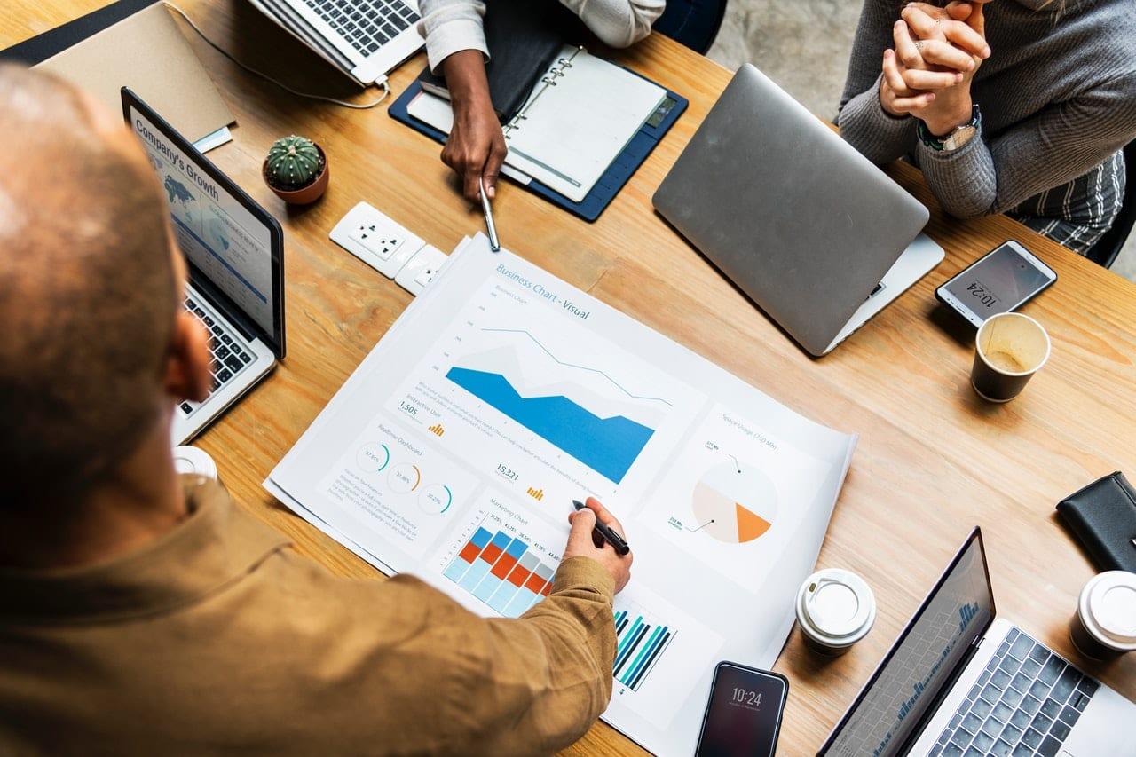 Seu portfolio não serve para conseguir clientes. Pessoas em reunião ao redor de uma mesa com vários acessórios (computadores, cadernos, gráficos etc.)