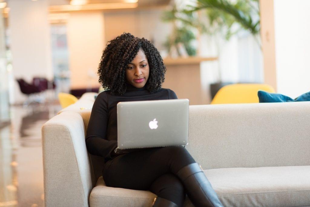 Quantos projetos colocar no portfolio: imagem de mulher com um laptop no colo, sentada em um sofá.